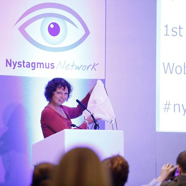 Sue Ricketts presenting on stage at a Nystagmus Network event. The stage is bathed in purple light and she stands at a podium in front of the Nystagmus Network logo.