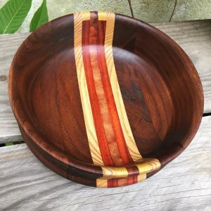 Small bowl with medium color wood, has red and yellow striped wood laminated through the middle.