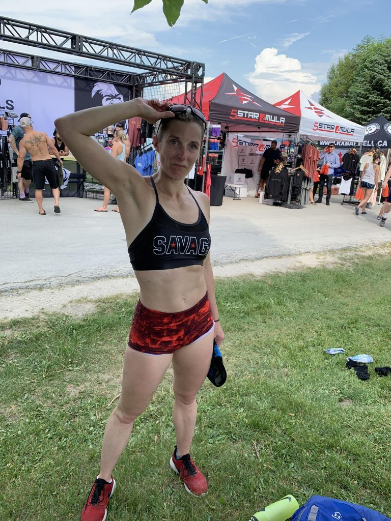 Kym - wearing lava-red shorts and a black sports bra that says Savage across the chest - smiles for the camera after a post-workout, cool-down dunk in Lake Huron.