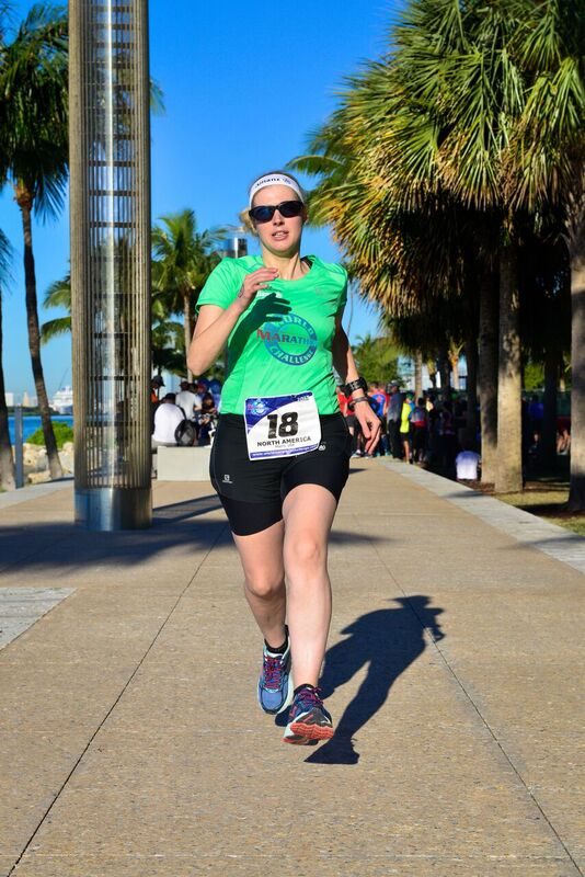 Sinead, wearing a bright green t-shirt, black shorts and dark glasses, runs confidently toward the camera. She's surrounded by palm trees. Photo credit: Mark Conlon, World Marathon Challenge